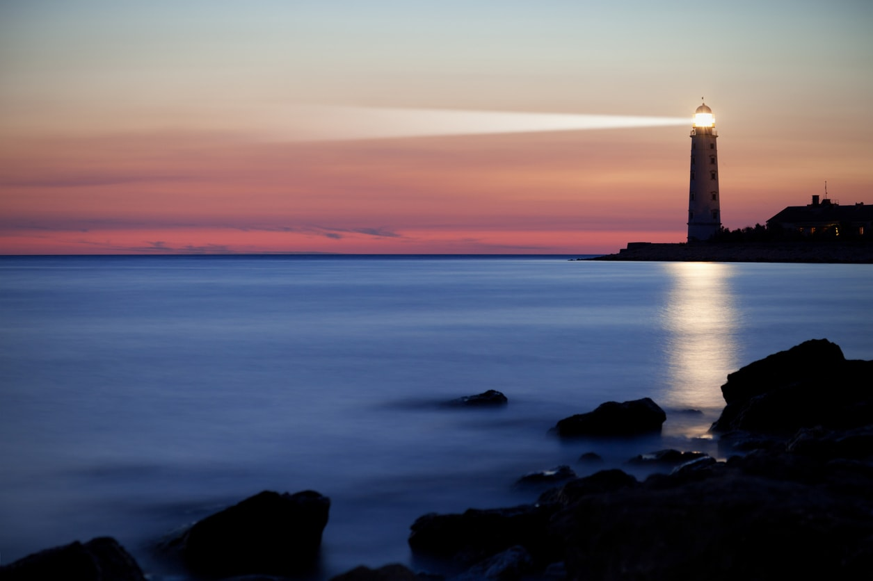 A lighthouse on the coast at sunset