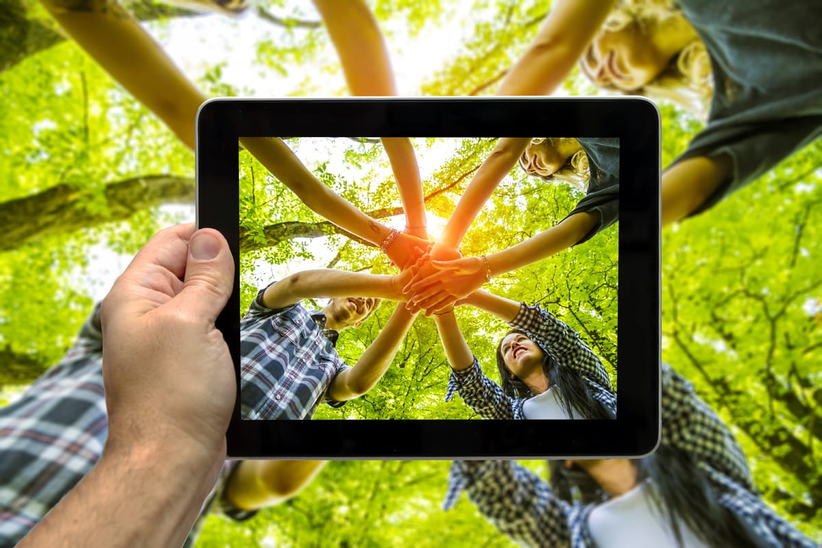 Group of people joining hands over an iPad frame