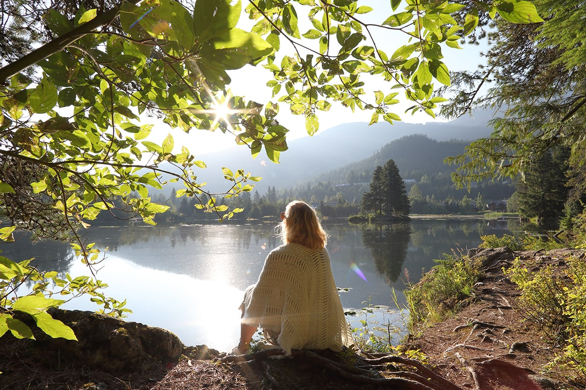 Woman relaxes on mountain lakeshore at sunrise