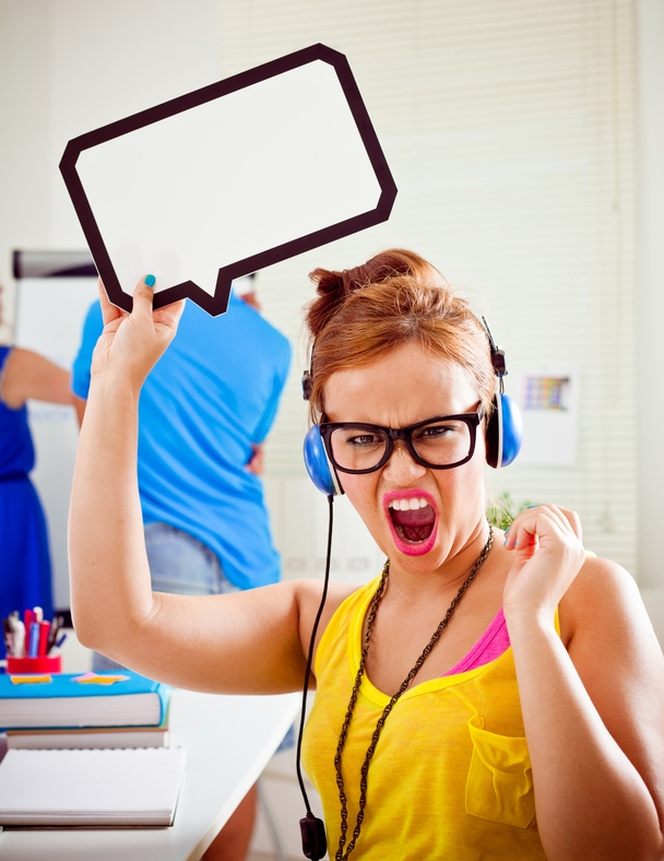 Young adult angry woman sitting in an office and holding speech bubble above her head, screaming at the camera.