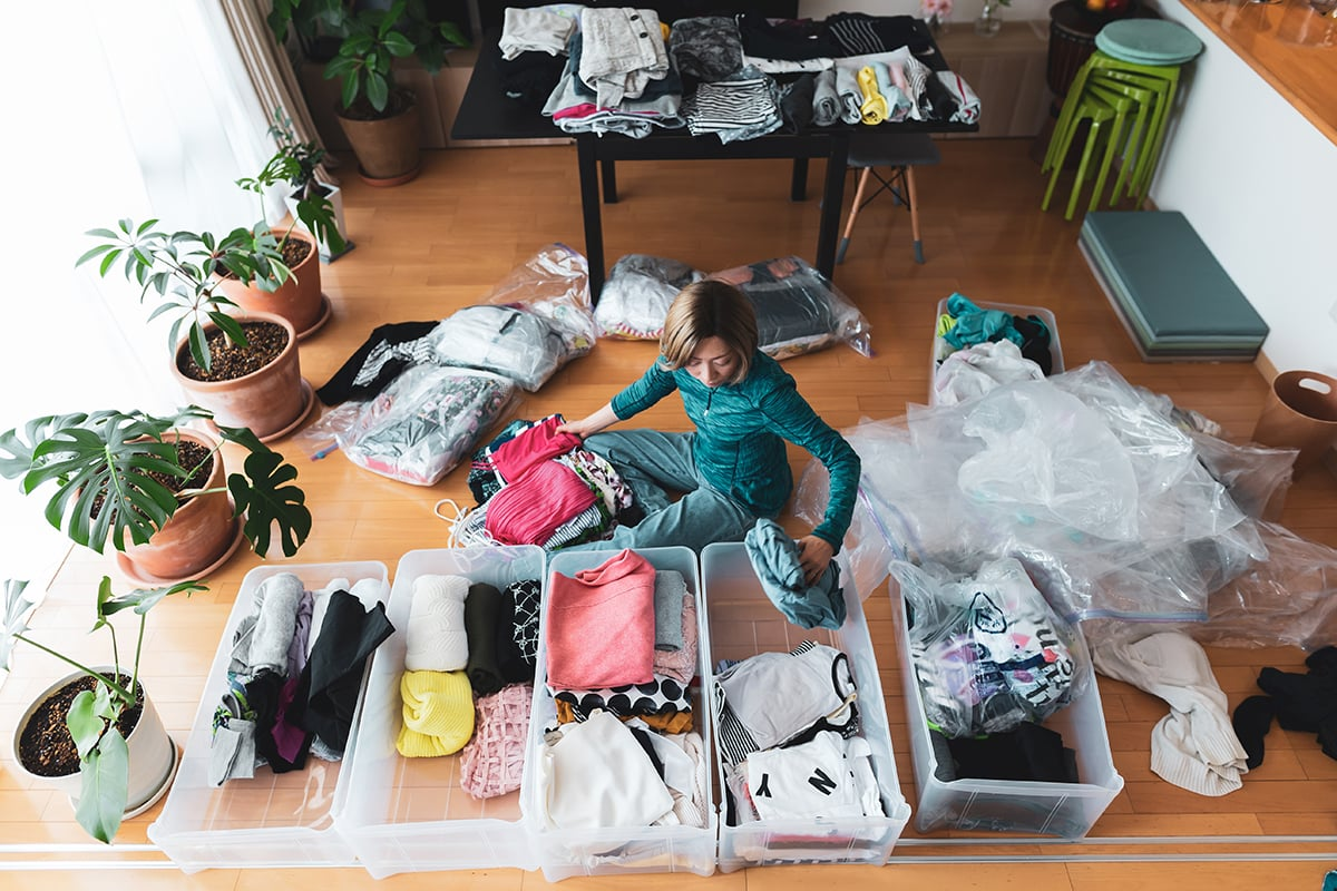 Woman organizes clothes in living room of her home