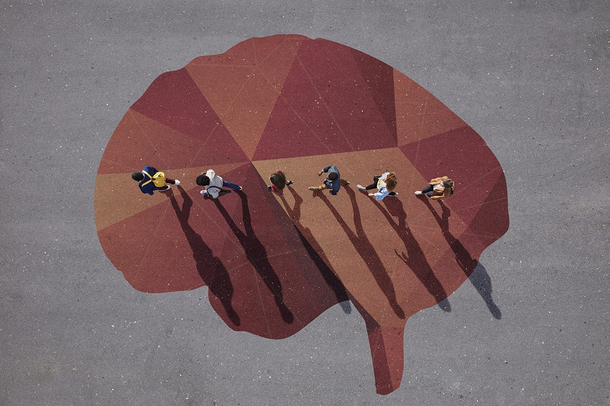 People walking in line across painted brain, on asphalt