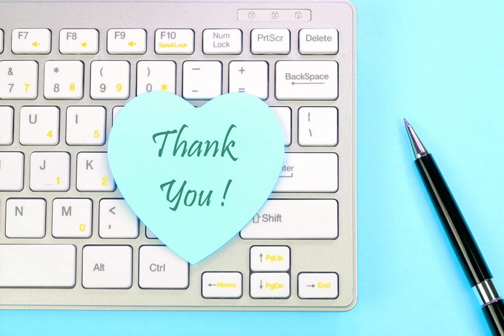 Thank You note text on a sticky note placed on a keyboard.