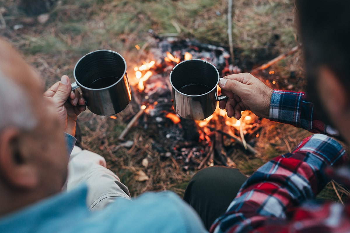 Photo of two generations males drinking coffee near fire in nature
