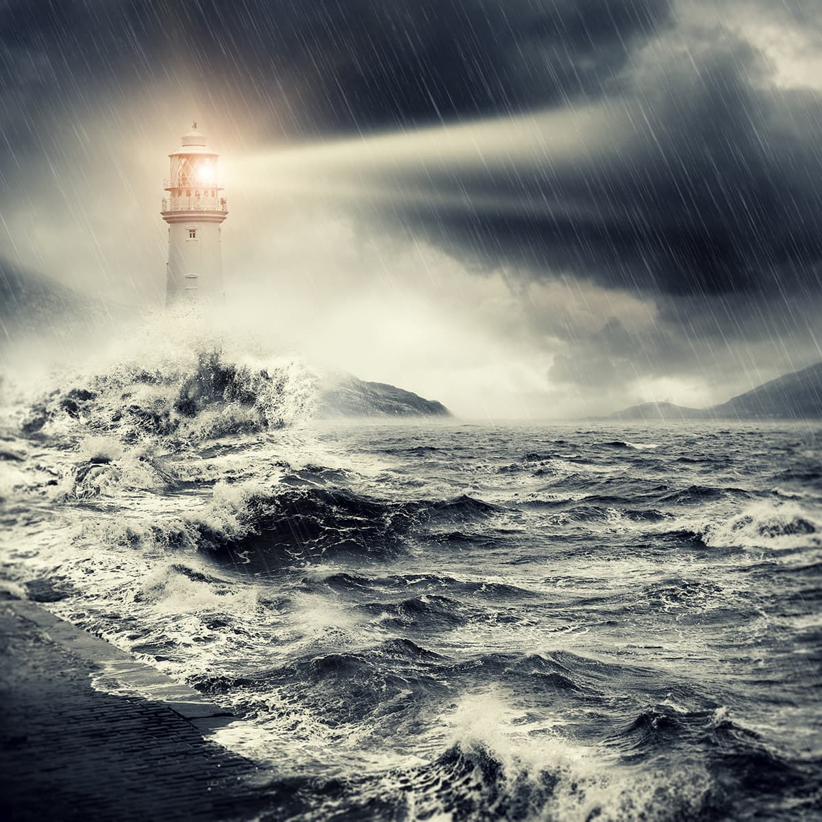 Lighthouse beacon shining over stormy seas