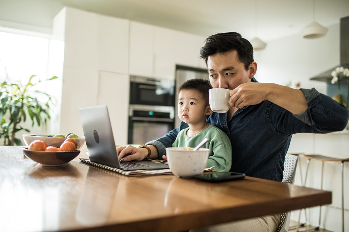 Father multi-tasking with young son (2 yrs) at kitchen table. Dad is drinking coffee and working on his computer.