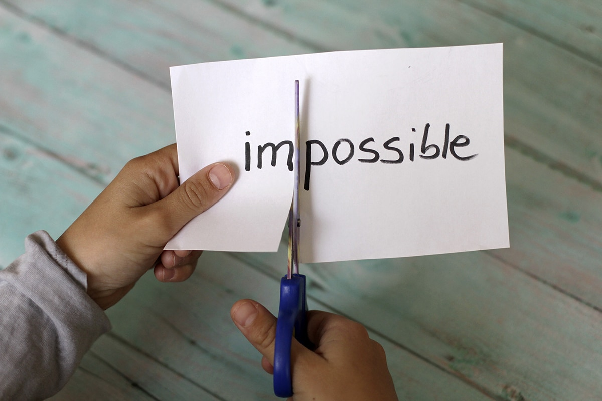 """Someone cutting the """"im"""" off the front of the word """"impossible"""" to change it to """"possible"""""""