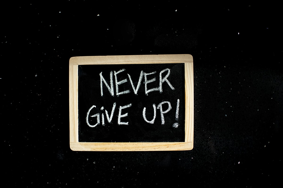 "Black Board with ""Never Give Up!"" written on it by white chalk."