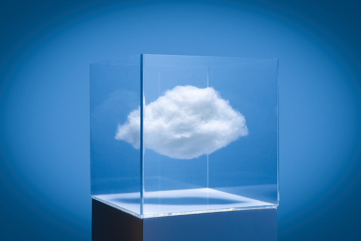 White puffy could in a transparent box on white pedestal, blue studio background