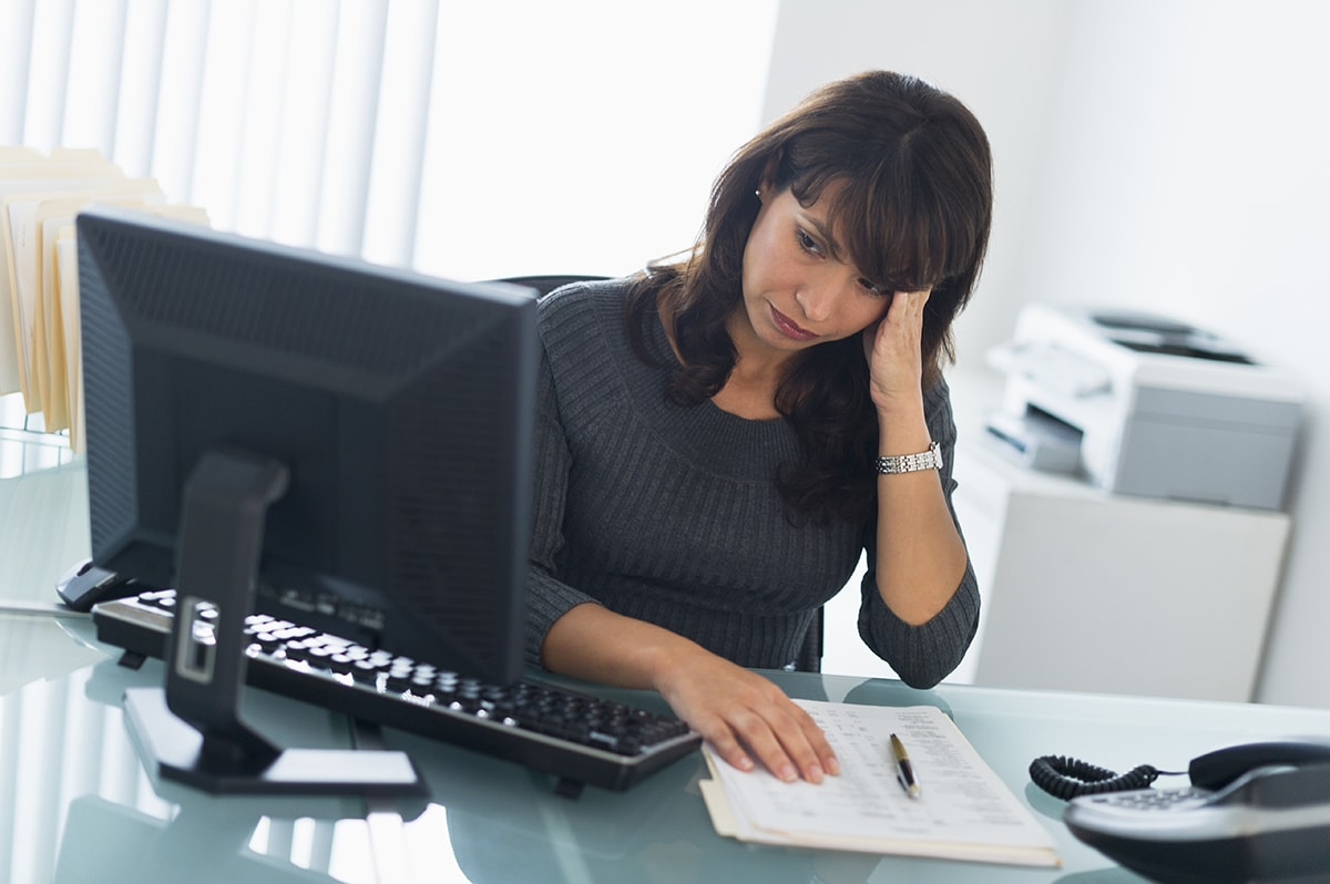 stressed female executive thinking at her computer